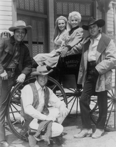 Cast photo from the television Western The Big Valley. From left: Richard Long, Linda Evans, Barbara Stanwyck, Peter Breck, and Lee Majors by wagon wheel.
